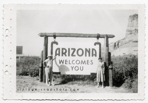 Man and woman pose next to Arizona welcome sign.