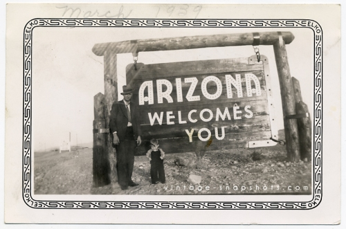1939 snapshot of a man and boy posing next to a sign welcoming travelers to Arizona.