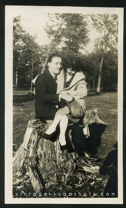 Vintage photo of a happy couple on tree stump, with photographer shadow.
