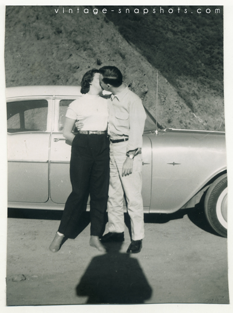 Vintage snapshot of a a couple kissing, with photographer shadow