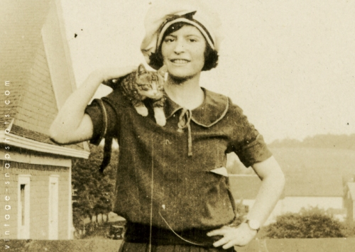 Vintage snapshot of woman with a cat on her shoulder.