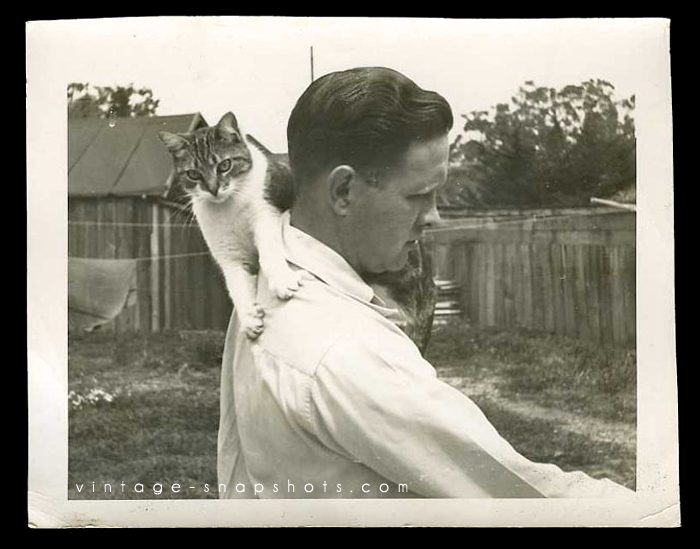 Vintage photo of a cat latching on to a man's shoulder.