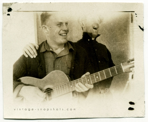 Vintage photo of men with a guitar, with light leak.