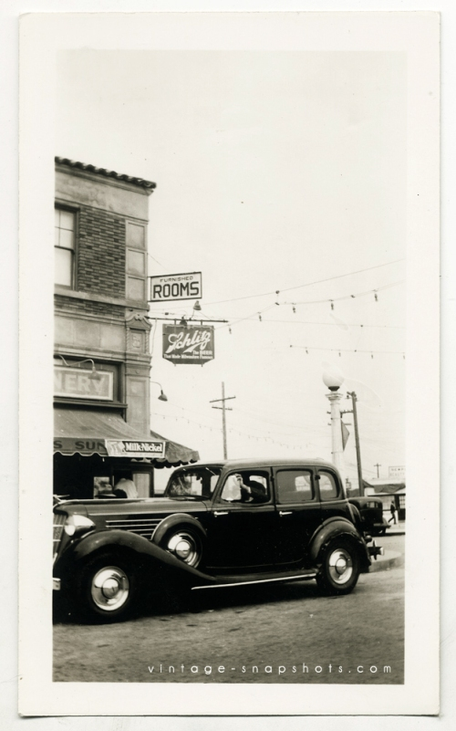 Vintage photograph of 1930s city scene with Schlitz sign