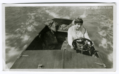Woman piloting a speedboat across the water in old photo from the 1920s