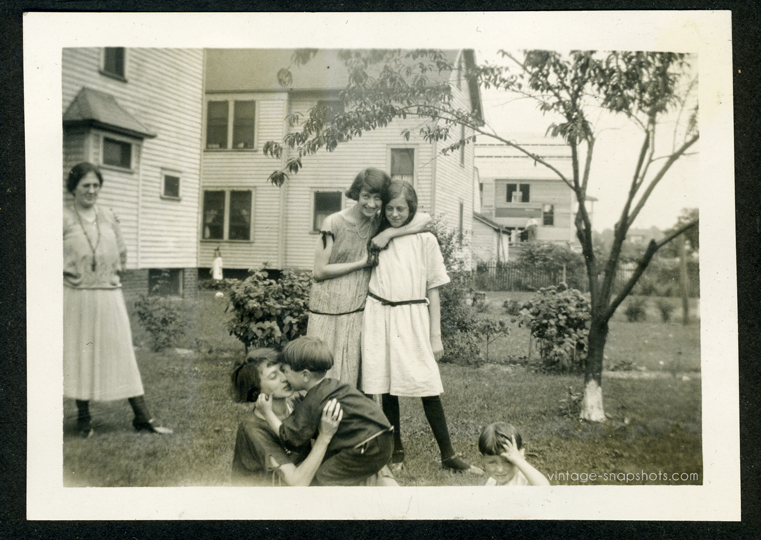 1920s photograph of females embracing, small girl in far background