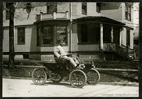 Man sits in early Ford automobile outside house while people stare through window