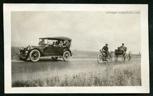 People in car marvel at a wagon towed by a motorbike in a 1920s photo