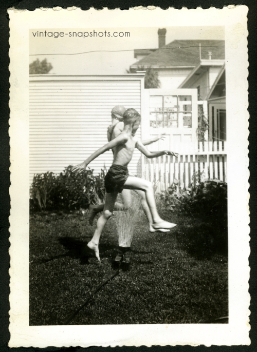 Vintage photo of a young boy and girl leaping over a sprinkler