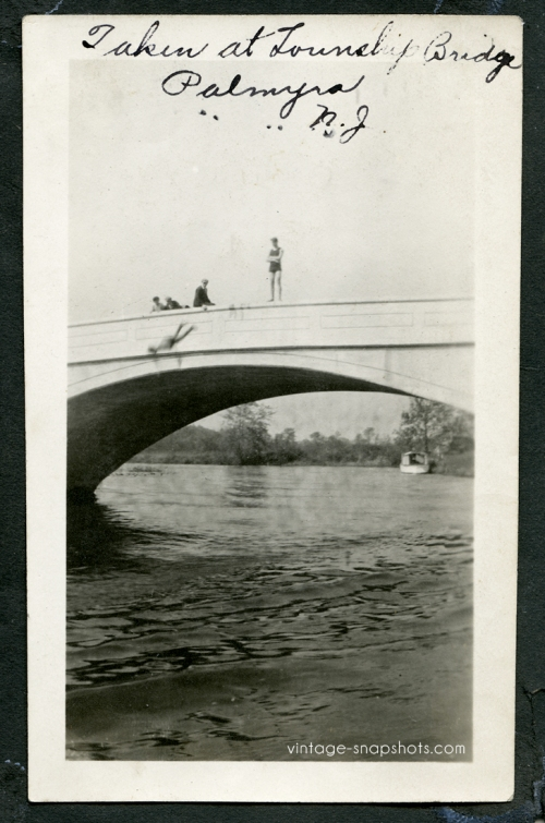 Vintage photo of person leaping from New Jersey bridge, circa 1910s, while their friends look on