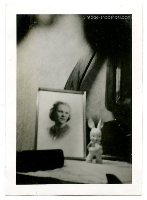 Odd, dreamy abstract photo of a framed portrait next to a bunny figure sitting on a table