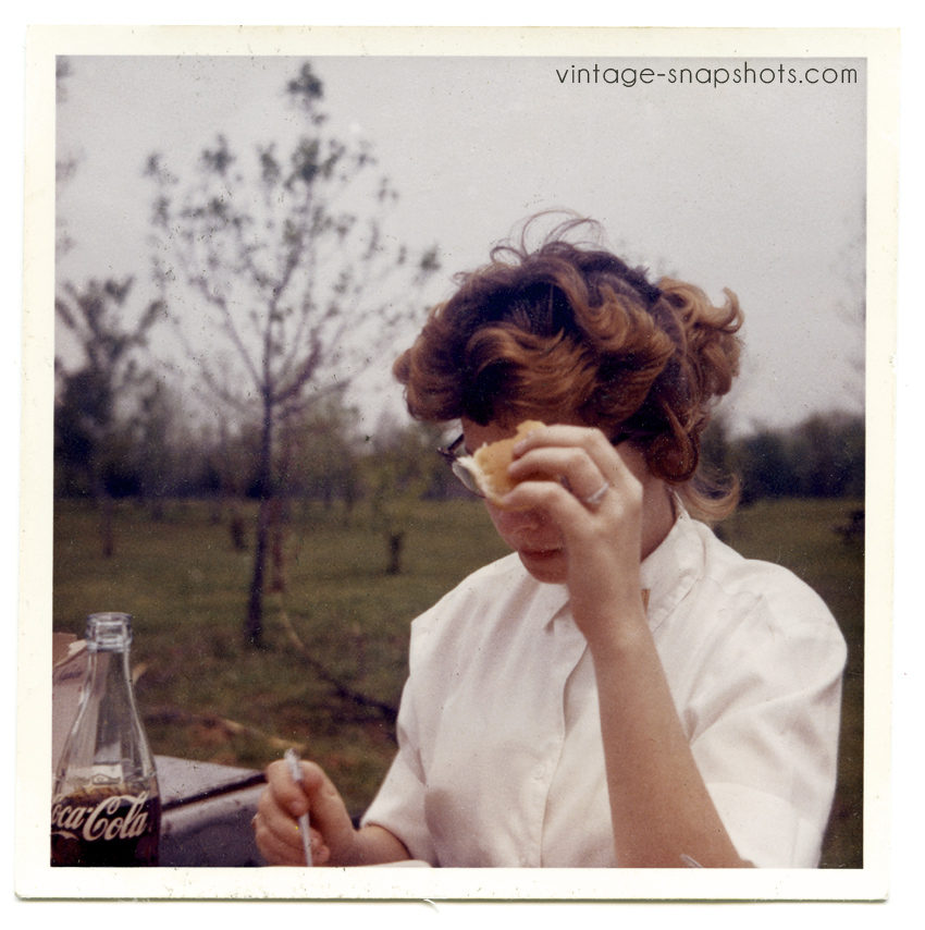 Quirky vintage c. 1960s photo of a woman eating, with Coke bottle and cat-eys glasses