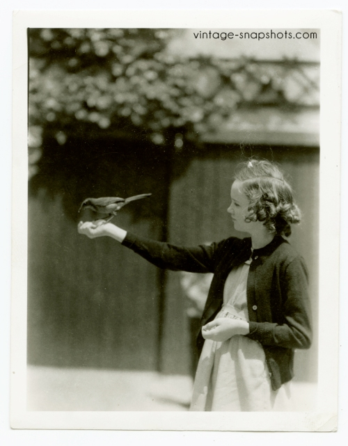 Vintage photograph of agirl holding a bird in her hand, circa 1940s