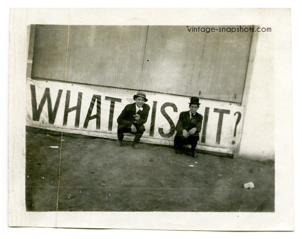 """Vintage photo of two men in front of a sign reading """"What is it?"""" (c 1907)"""