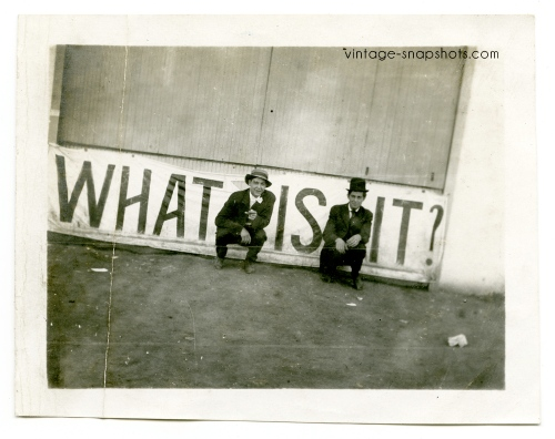 "Vintage photo of two men in front of a sign reading ""What is it?"" (c 1907)"