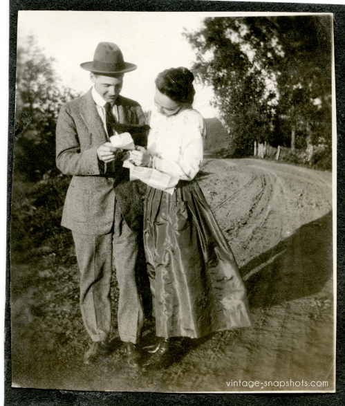 Circa 1911 vintage snapshot of a couple reading what may be a letter