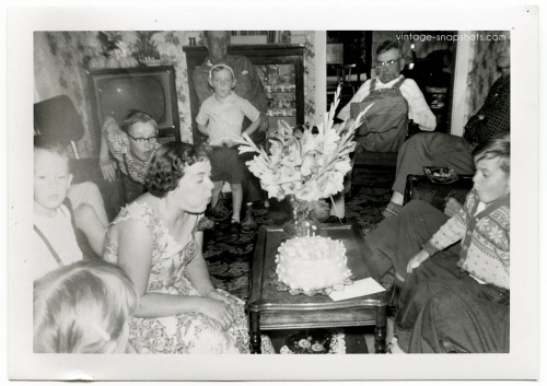 1950s family at birthday party, kids blowing out candles on cake
