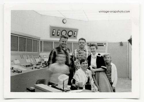 Vintage snapshot of 1950s family, with boy's face a blur