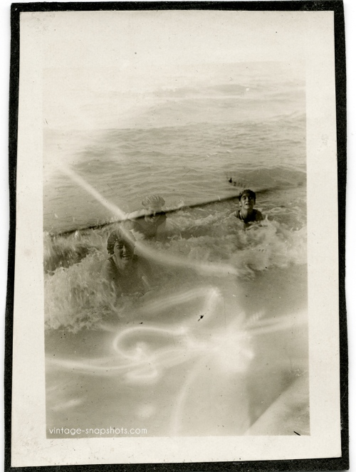 Odd vintage photo with strange light effect over people pictured in surf
