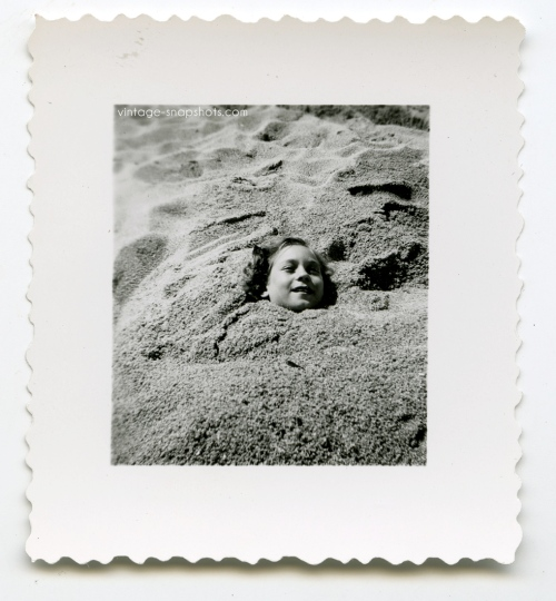 Vintage snapshot photo of girl buried in sand at the beach