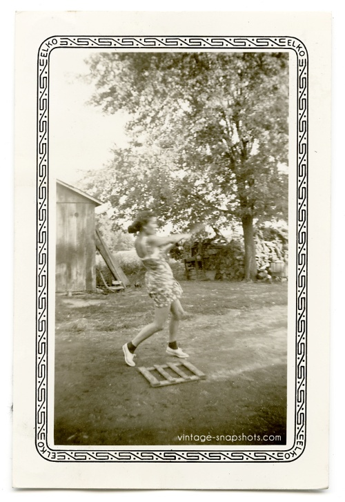 Vintage Elko-border photo of a woman swinging a baseball bat while standing at a home-made home plate