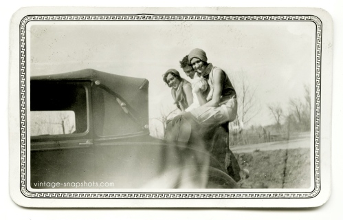 Vintage snapshot of three people sitting atop a rumble seat