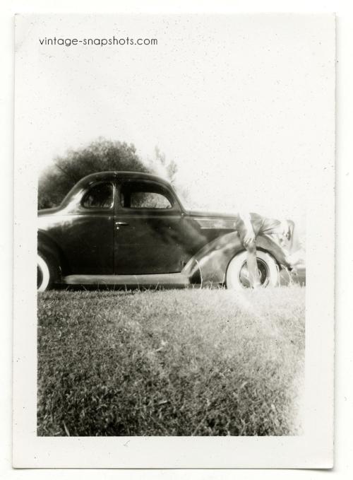 Vintage snapshot with odd light leak/mistake obscuring man sitting on car