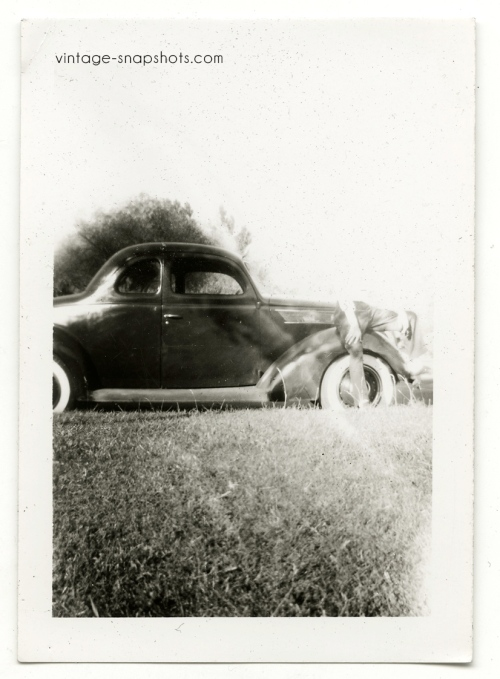 Vintage snapshot with odd light leak/mistake obscuring man sitting on car