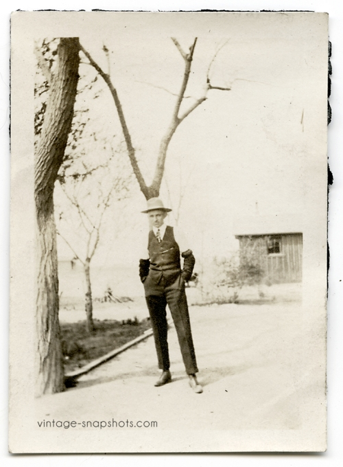 Vintage photo of a man standing in front of a tree, with the branches appearing to rise from his hat