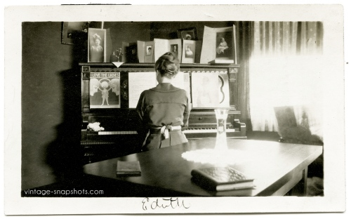 Vintage photo of woman named Edith playing the piano with sheet music and family photos on the instrument