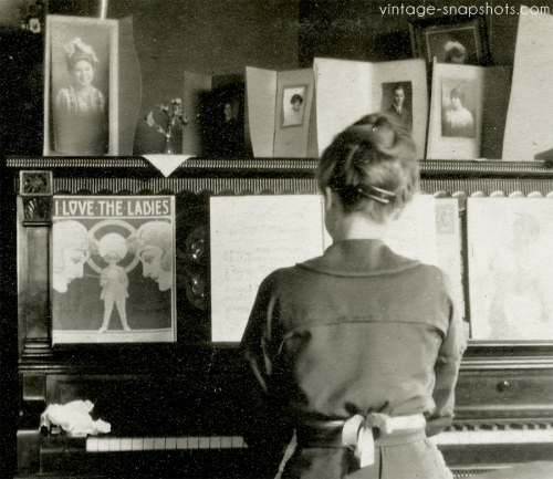 Vintage snapshot of woman playing piano, with sheet music and family portraits on piano
