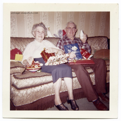 Vintage snapshot of older man displaying his Christmas present, a bottle of Old Spice