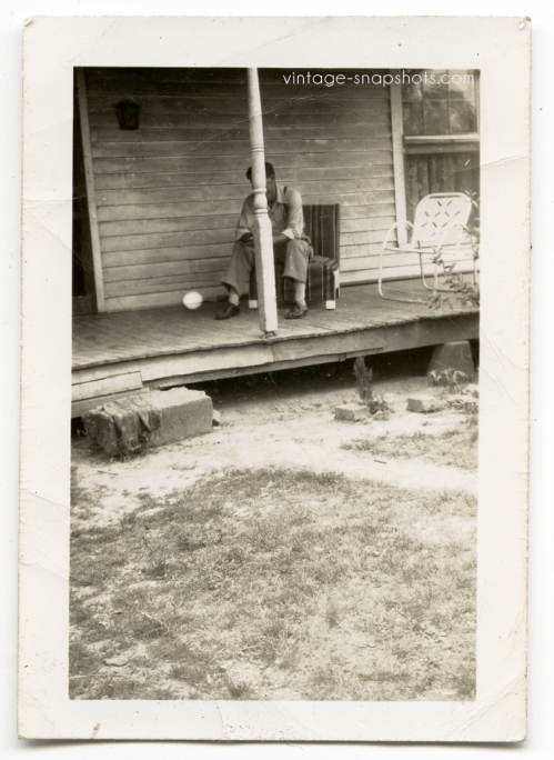 Vintage photo of man on porch with post in way of his face