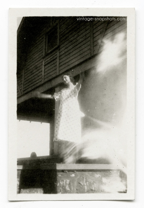 Vintage 1920s snapshot of woman standing with her arms outstretched