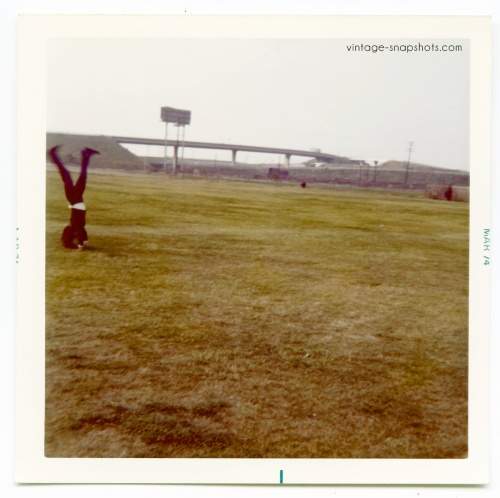 Strange vintage 1970s color snapshot of person  doing a handstand in an open field
