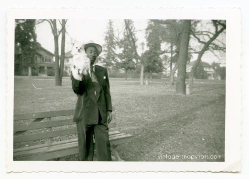 c 1940/50s Black Man Holds White Dog Up for Snapshot