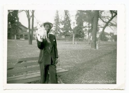 c 1940/50s Black Man Holds White Dog Up for Snapshot