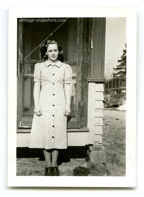Vintage 1930s snapshot of girl in front of screen door