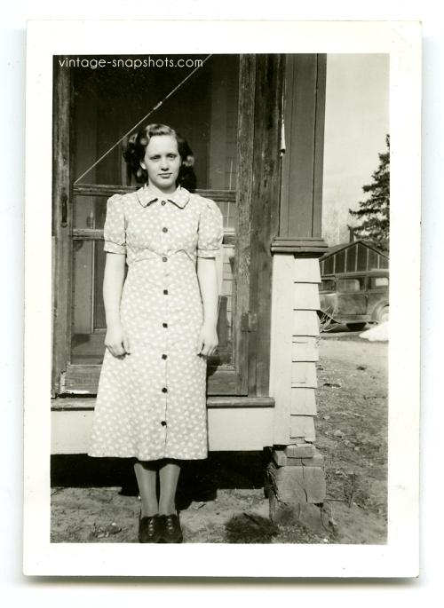 Vintage 1930s snapshot of girl in front of screen door