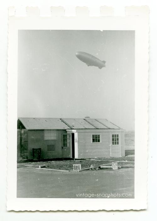 Vintage snapshot of shack plus blimp overhead