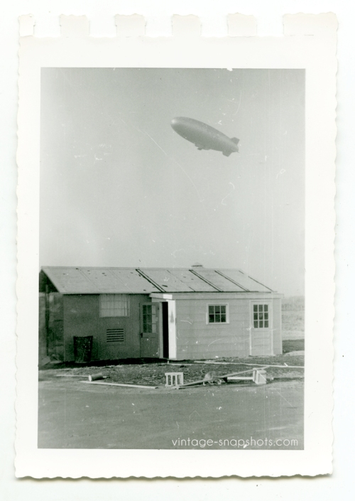 Vintage snapshot of shack plus blimp overhead