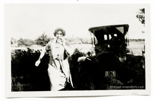 Circa 1920s snapshot of woman running, with parked car in background