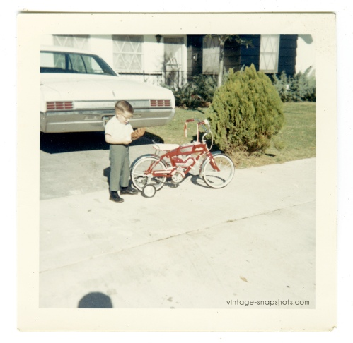 Vintage 1960s photo of serious boy looking at his baseball glove alongside his red bicycle