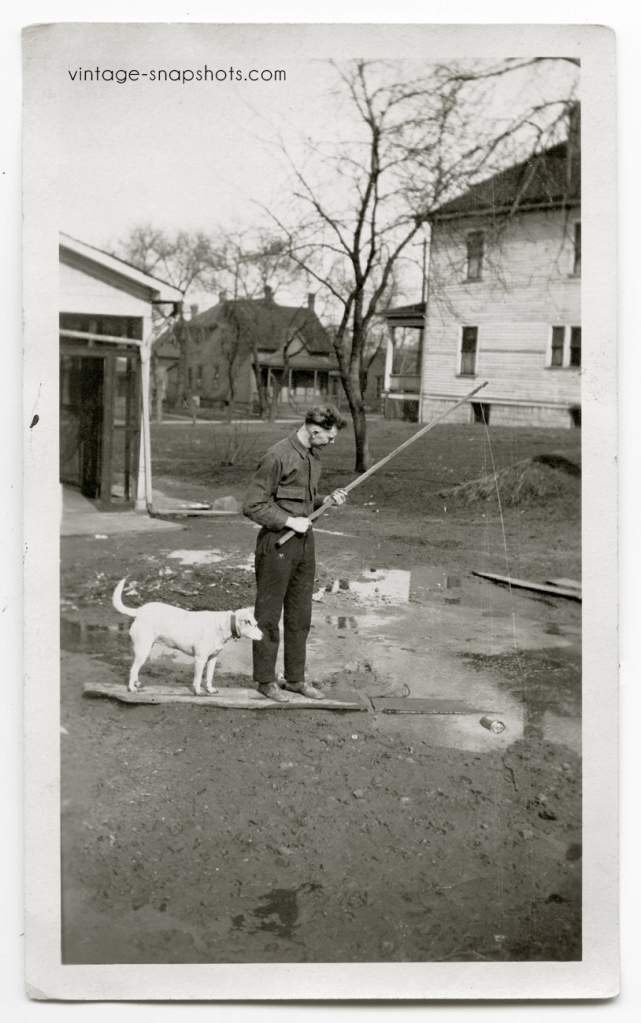 "Funny vintage snapshot featuring an and dog ""fishing"" in what seems to be a backyard"