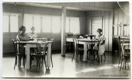 Circa 1920s vintage photo of women sitting alone at dining tables