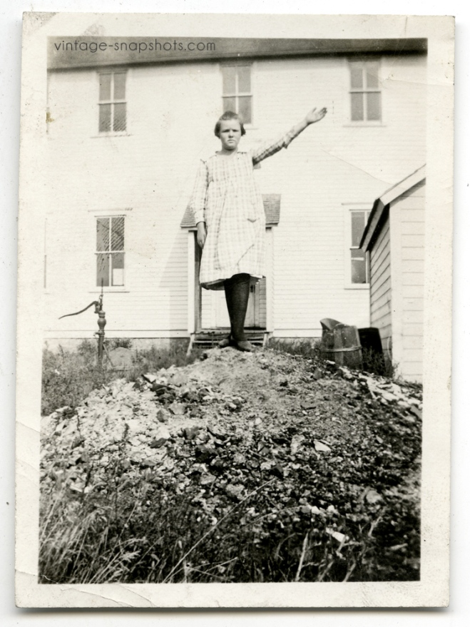 """Vintage circa 1920s snapshot of girl standing on top of small """"hill"""""""