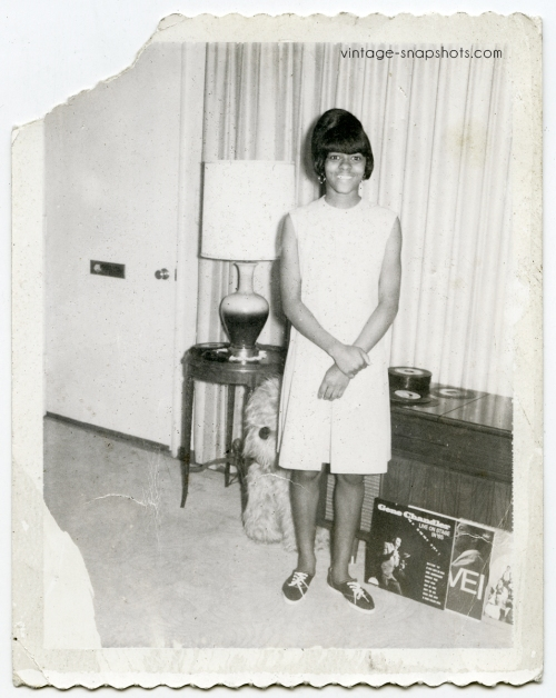 1960s snapshot of cute Black girl posing with record albums and singles