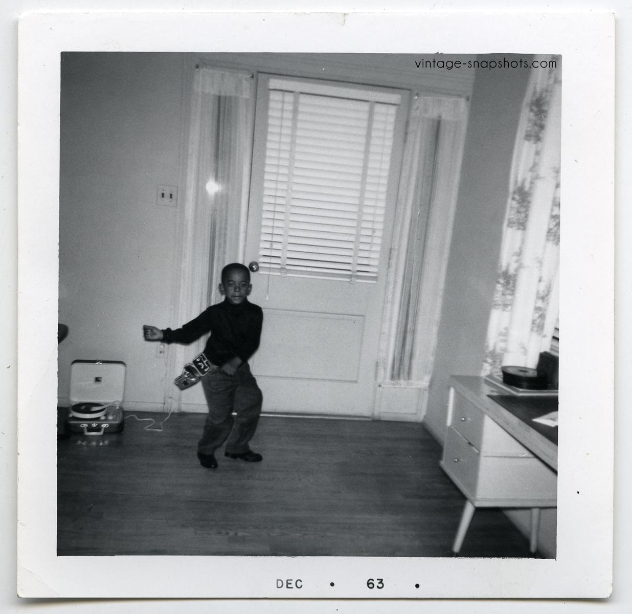 1963 vintage snapshot photograph of black boy dancing to record player while wearing toy gun