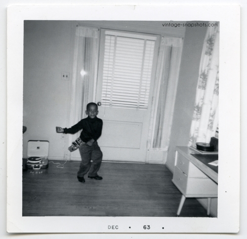 1963 vintage snapshot photograph of black boy dancing to record player while wearing toy gun