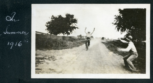 Vintage 1916 snapshot of man with arms raised riding a bike down a country road